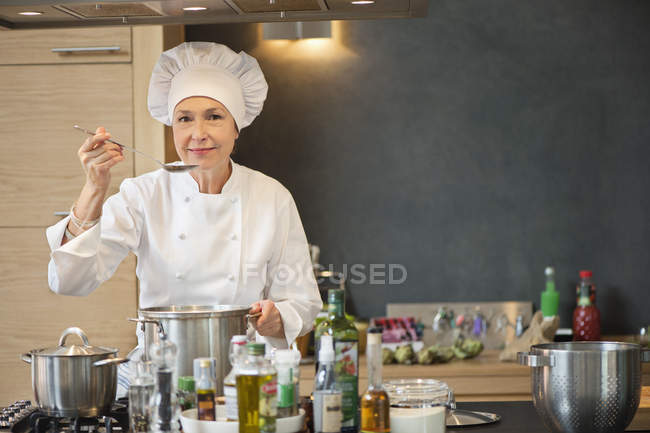 Woman in chef costume tasting food in kitchen — Stock Photo
