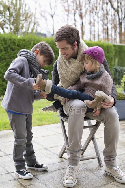Мальчик надевает обувь на сестру, сидя на коленях отца на открытом воздухе — стоковое фото