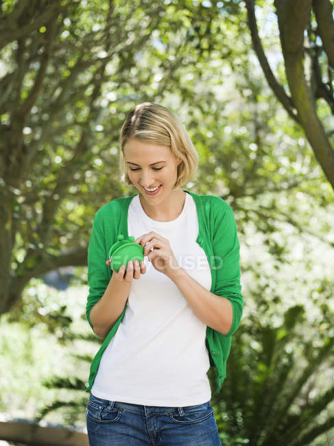 Smiling blond woman holding pouch bag in garden — Stock Photo