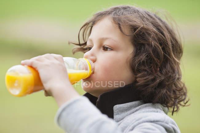 Крупный план мальчика, пьющего сок из бутылки на открытом воздухе — стоковое фото