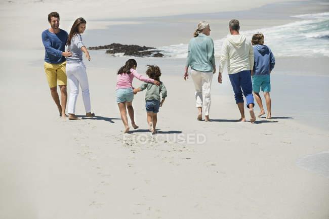 Família feliz andando na praia arenosa — Fotografia de Stock