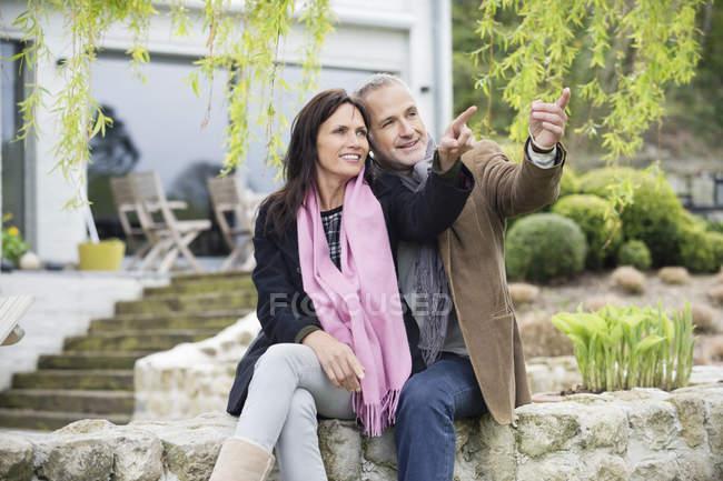 Романтична пара, сидячи в саду і дивитися вбік — стокове фото