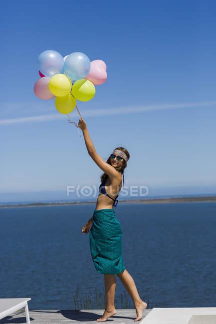 Счастливая стильная женщина, держащая воздушные шары на фоне голубого неба — стоковое фото