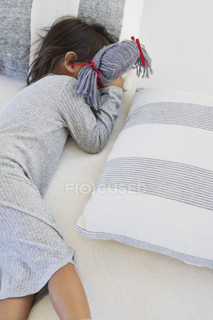 Cute little girl sleeping on bed with rag doll — Stock Photo