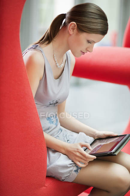 Young confident businesswoman using digital tablet in office — Stock Photo