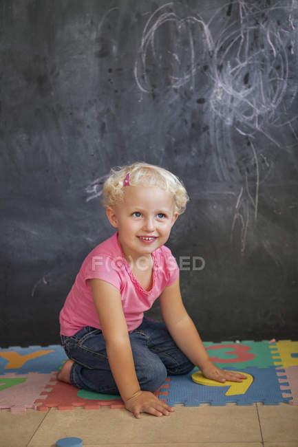 Sonriendo linda niña jugando con el número de rompecabezas delante de una pizarra - foto de stock