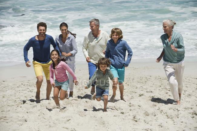 Счастливая семья веселится на песчаном пляже — стоковое фото