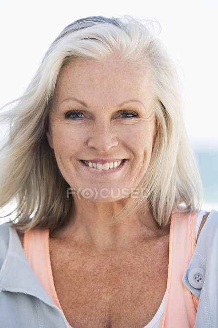 Portrait of smiling senior woman on beach — Stock Photo