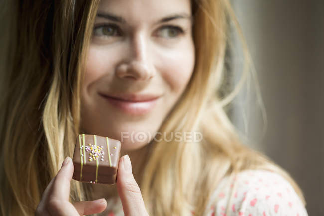 Woman holding chocolate candy and looking away — стоковое фото