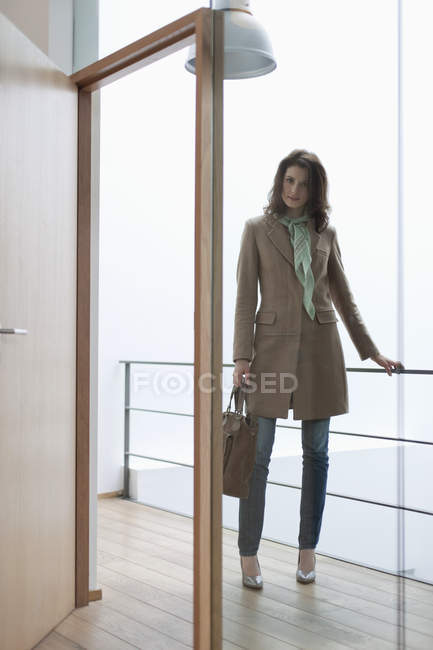 Elegant woman with handbag standing at doorway — Stock Photo
