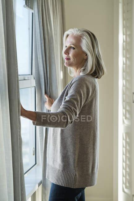 Заботливая пожилая женщина, стоящая у окна дома — стоковое фото