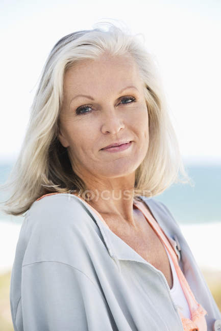 Portrait of elegant senior woman smiling on beach — Stock Photo
