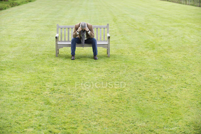 Depressed man sitting on wooden bench in green field — Stock Photo