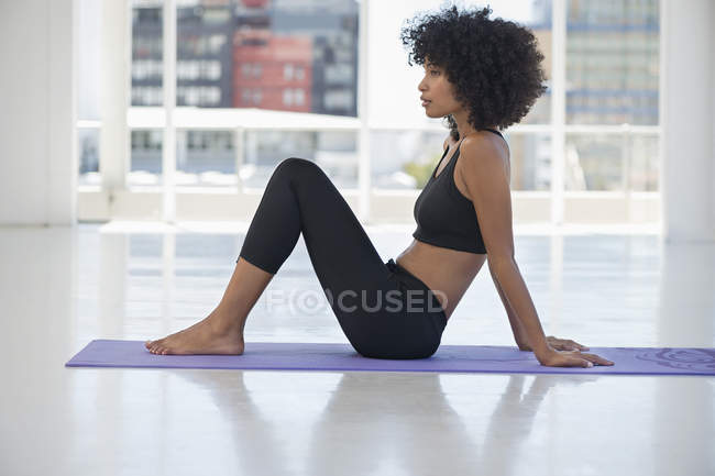 Woman practicing yoga on exercise mat — Stock Photo