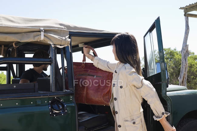 Woman putting bag in vehicle for travelling — Stock Photo
