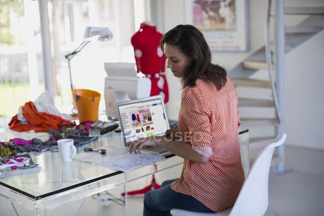 Konzentrierte Modedesignerin liest Zeitung im Büro — Stockfoto