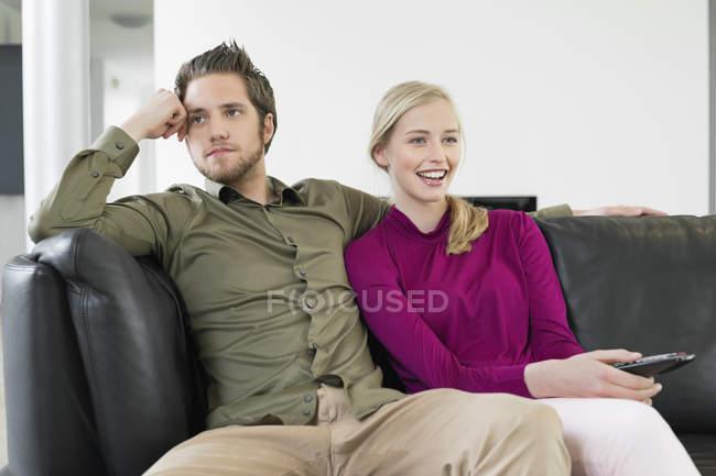 Couple, regarder la télévision sur le canapé dans le salon — Photo de stock