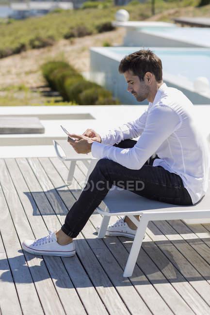 Selbstbewusster Mann nutzt Smartphone auf Terrasse in der Natur — Stockfoto