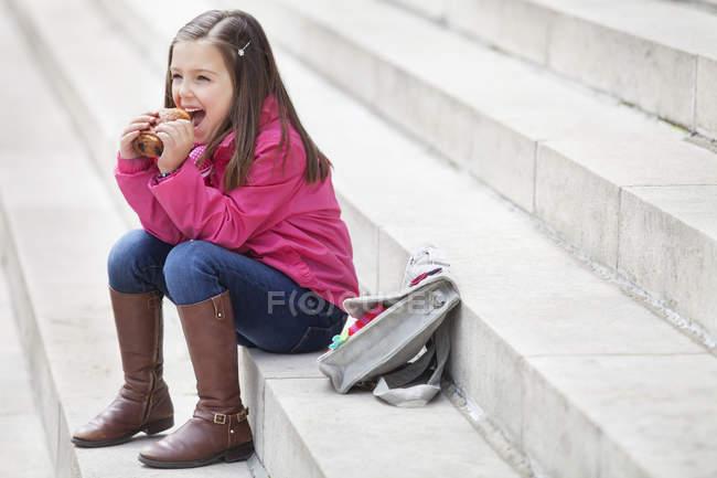 Estudante que senta-se em etapas e que come o Chocolat do au — Fotografia de Stock