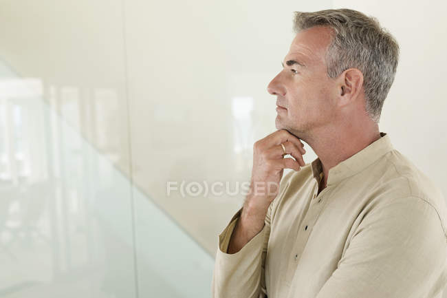 Thoughtful mature man standing in front of wall — Stockfoto
