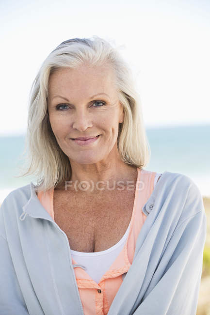 Portrait d'une femme senior souriante sur la plage — Photo de stock