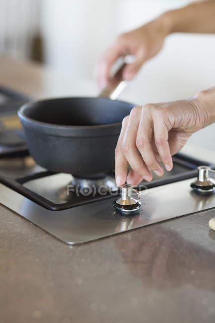 Жіночих рук, поклавши каструлю на газ піч кухні — стокове фото