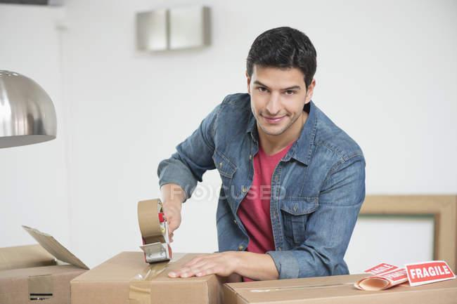 Homme scotchant vers le haut de la boîte en carton à la maison et regardant l'appareil-photo — Photo de stock