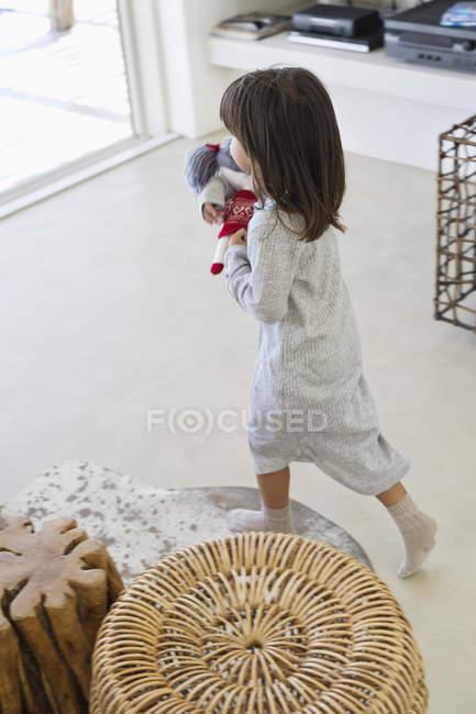 Маленькая девочка с тряпичной куклой дома — стоковое фото