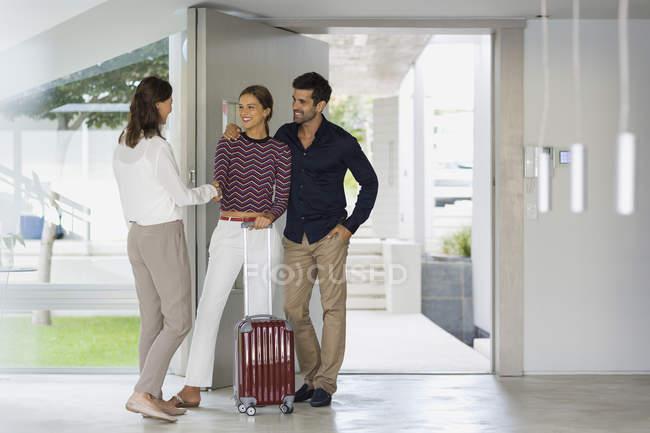 Mujer feliz dando la bienvenida a amigos en casa - foto de stock