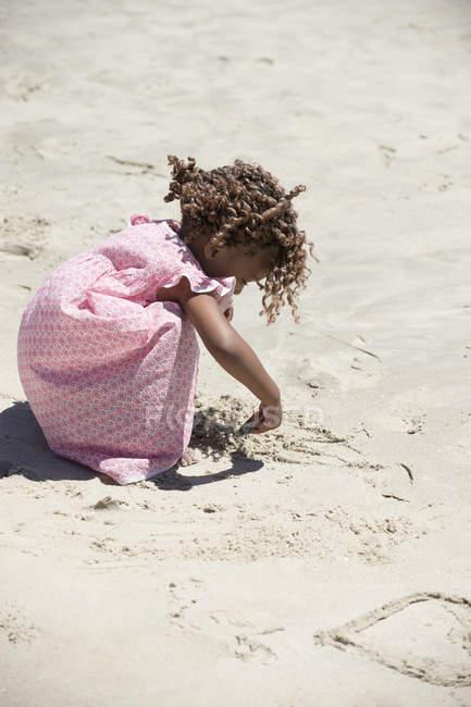 Petite fille en robe rose jouant avec le sable sur la plage — Photo de stock