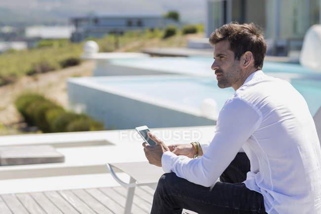 Man holding smartphone deckchair on terrace — Stock Photo