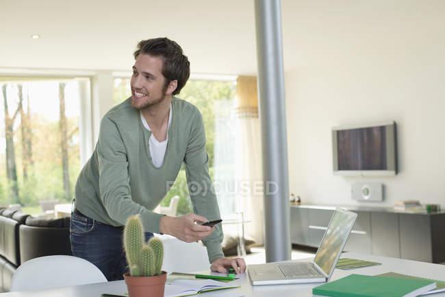 Улыбающийся человек работает на ноутбуке и держит мобильный телефон — стоковое фото