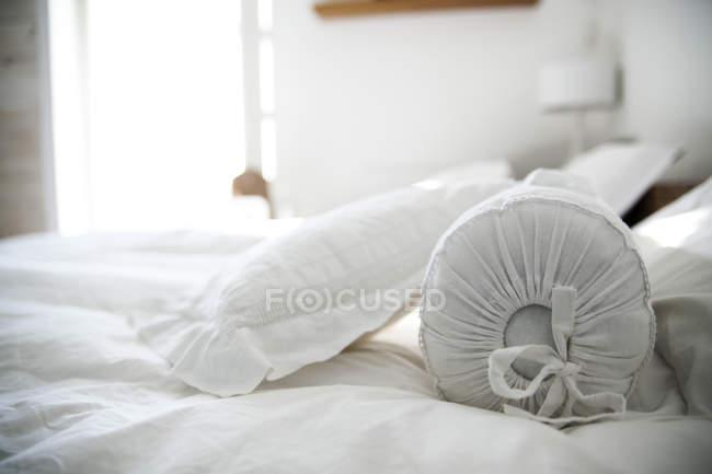 Kissen auf weißem Bett im hellen Schlafzimmer — Stockfoto