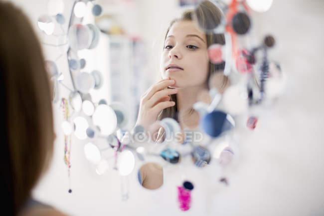 Menina adolescente pensativo olhando para o espelho — Fotografia de Stock