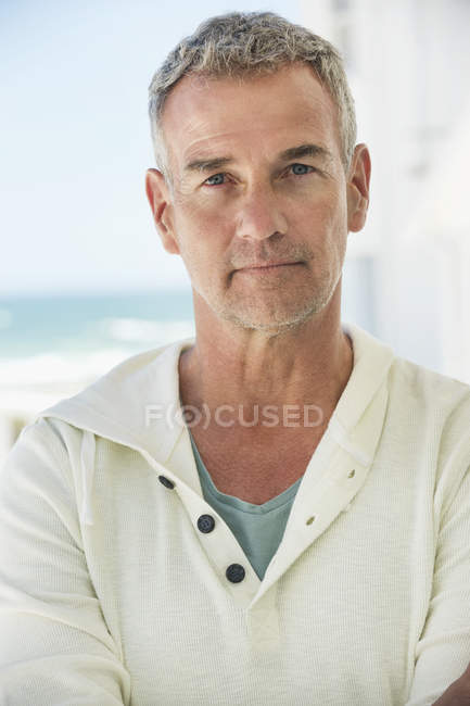 Portrait of thoughtful confident mature man looking at camera outdoors — Stock Photo