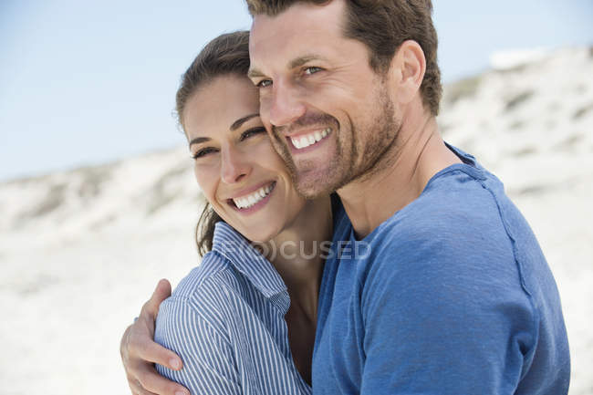 Крупный план счастливой романтической пары, обнимающейся на пляже — стоковое фото