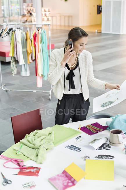 Diseñadora de moda hablando por teléfono móvil en la oficina - foto de stock