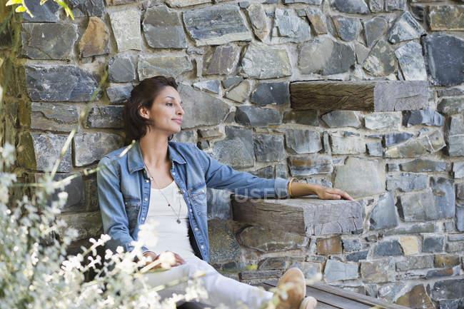 Frau lehnt an Steinmauer und träumt vom Tag — Stockfoto