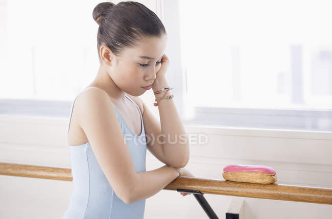 Little ballerina looking displeased while looking at eclair — Stock Photo