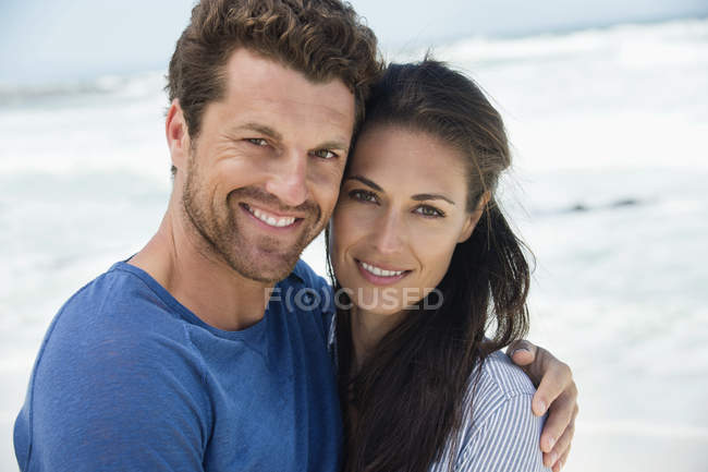 Porträt eines glücklichen romantischen Paares, das sich am Strand umarmt — Stockfoto