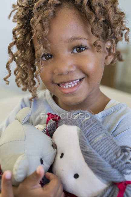 Portrait of cute little girl holding dolls and smiling — Stockfoto