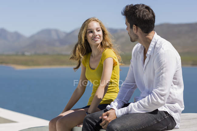 Close-up of smiling couple looking at each other while sitting on wall in nature — Stock Photo