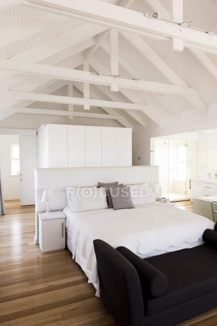 Interior of modern light cozy bedroom with wooden floor — Stock Photo