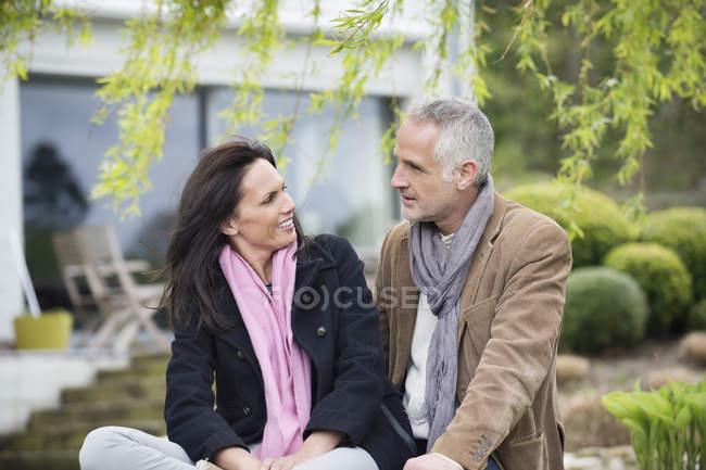 Couple romantique souriant assis dans le jardin à la campagne — Photo de stock