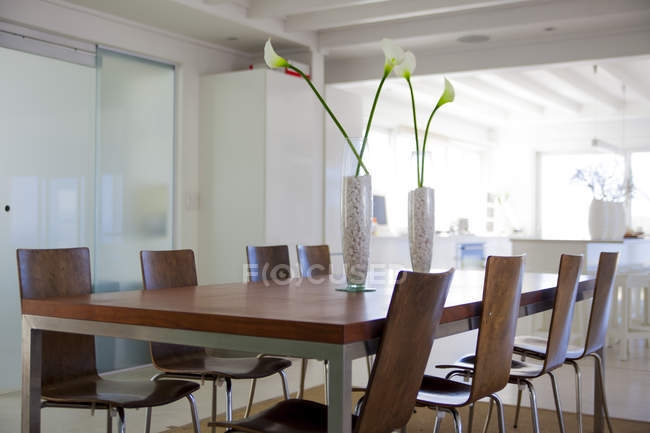Interior of modern dining room with flowers on table — Stock Photo