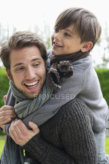 Happy boy riding piggyback on father — Stock Photo