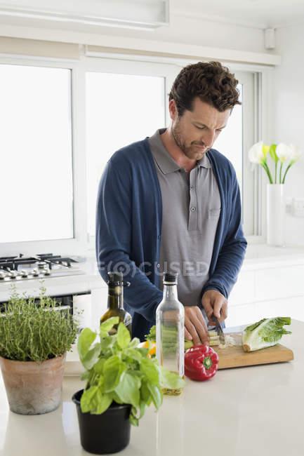 Портрет улыбающегося мужчины, рубящего овощи на кухне — стоковое фото