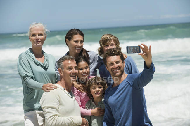 Portrait of happy multi-generation family taking selfie with cell phone on beach — Stock Photo