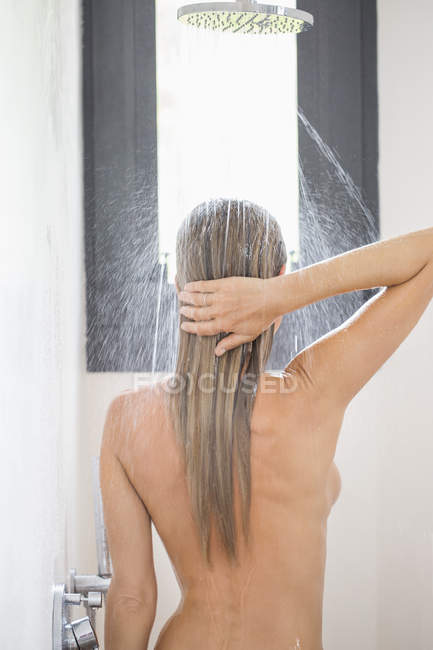 Rear view of naked sensual woman taking shower in bathroom — Stock Photo