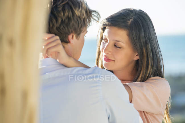 Romantic couple standing face to face on beach — Stock Photo
